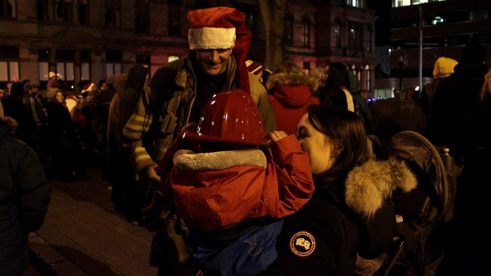 Dave Pace gives a child a firefighter helmet before the tree lighting.