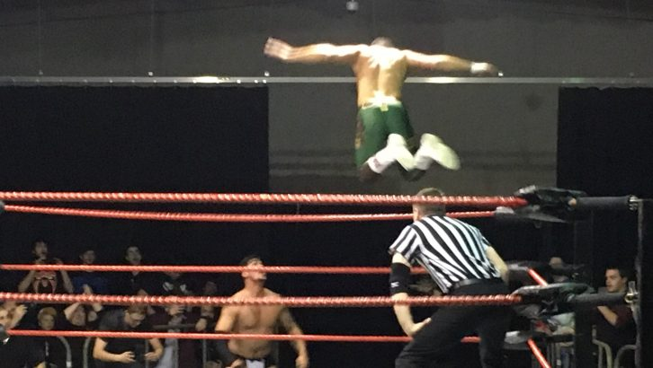 Cody Rhodes (in green) launches a flying attack on Dick Durning.