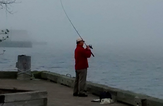 A man fishes off the boardwalk near Bishop's Landing.
