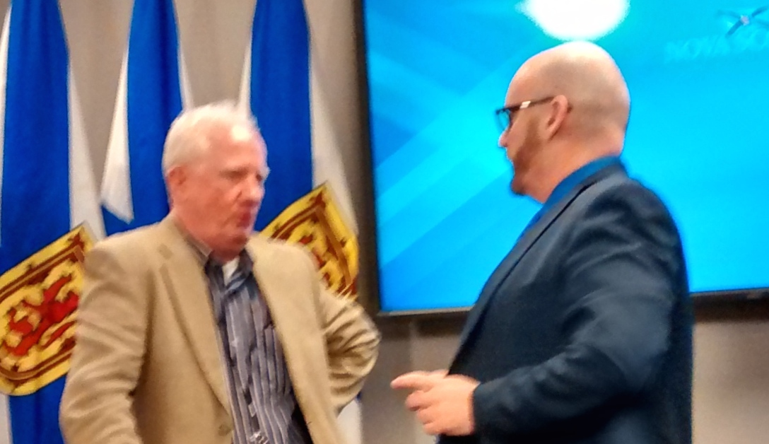Michael Pickup (right), speaks to a colleague at Wednesday's news conference.