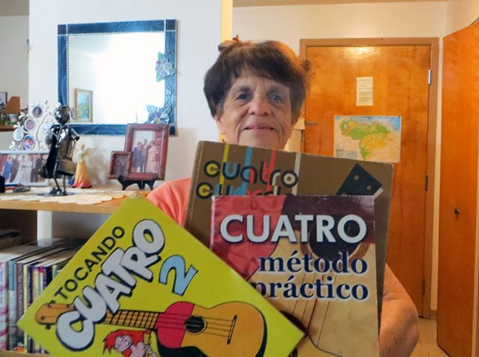 Maria Peña holding musical instruction books from Venezuela.