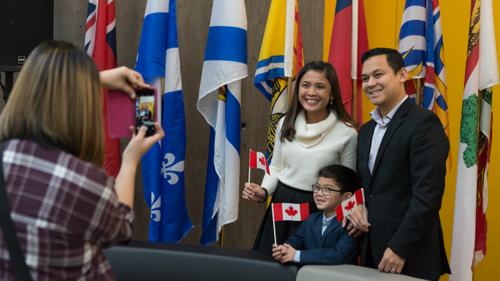 The Cuarentas family posing in front of several flags at their citizenship ceremony