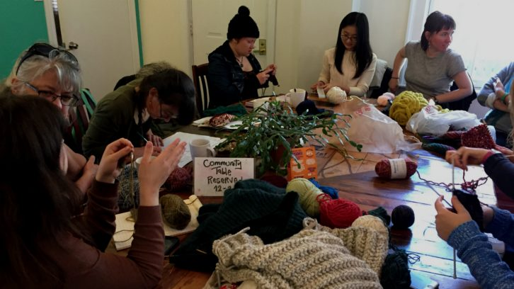 Jessica Melindy (far-right) talks with participants at her monthly knitting group In Gauge in a cafe in Halifax.