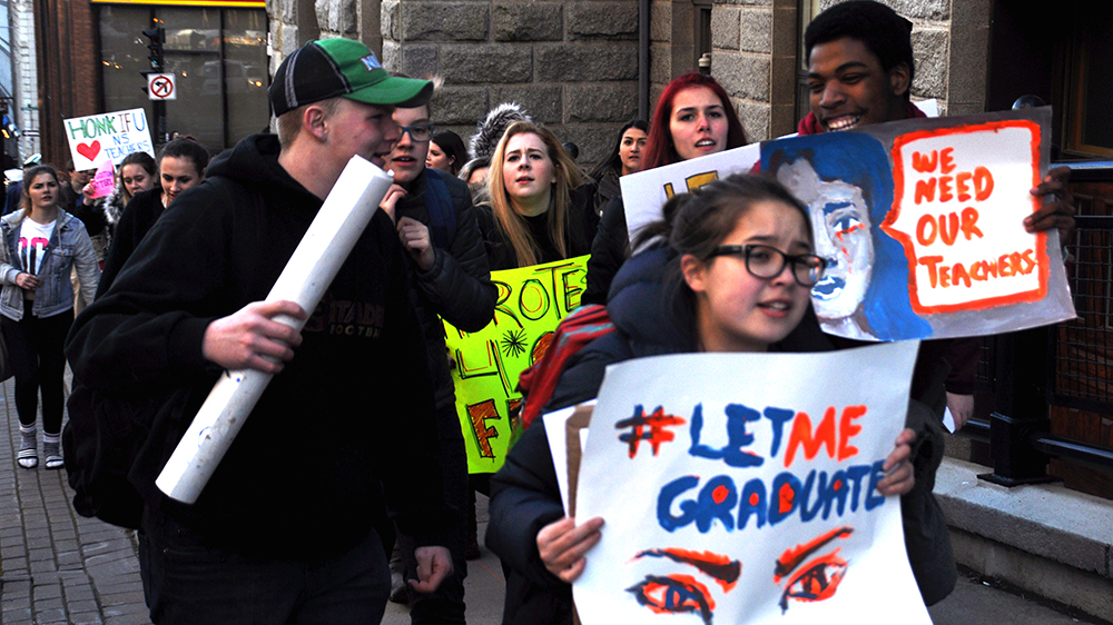 Students walk on the street in supporting for their teachers.