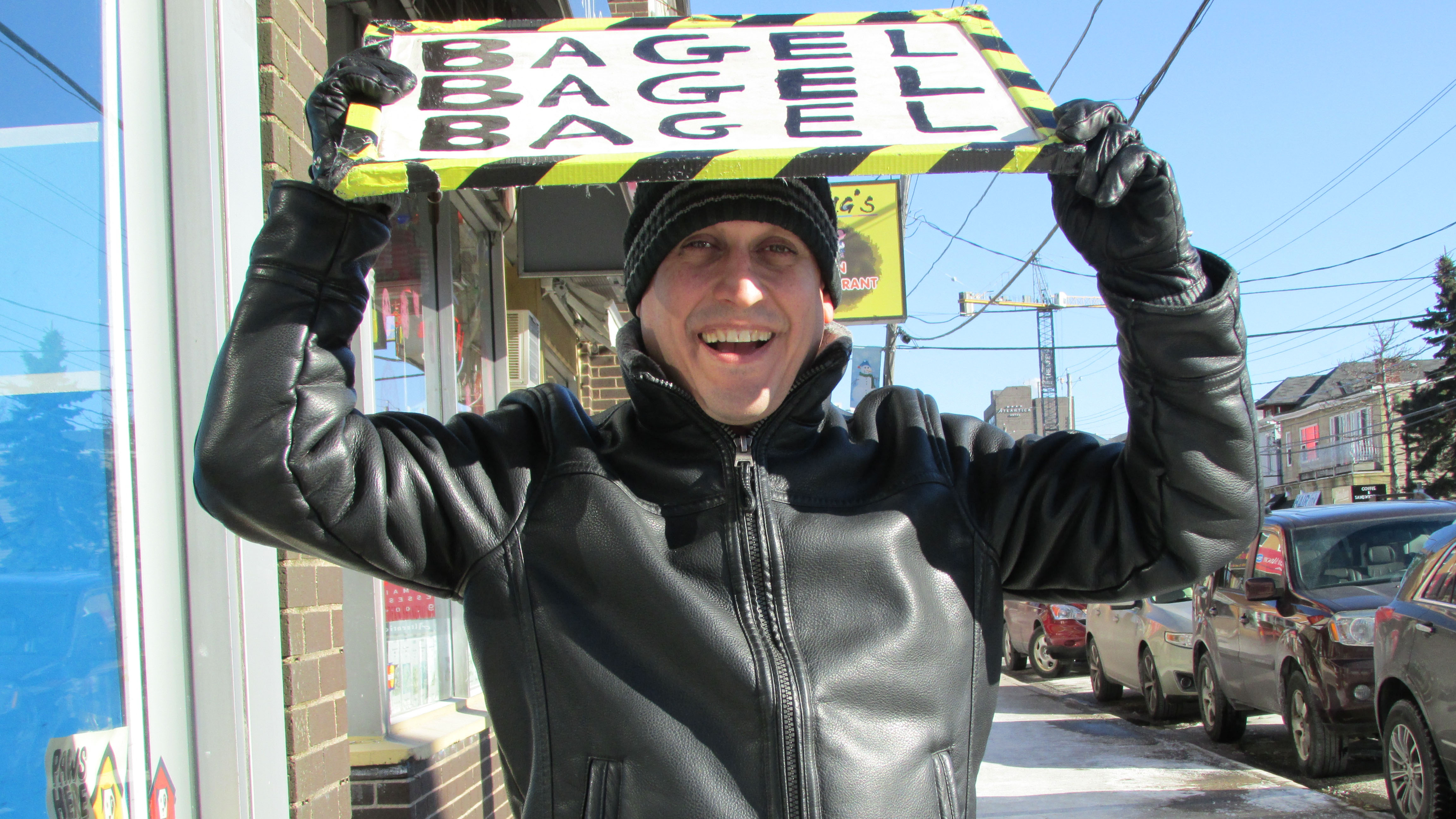 Gerry Lonergan, owner of the East Coast Bakey, spins his sign and ushers pedestrians inside for some bagels.