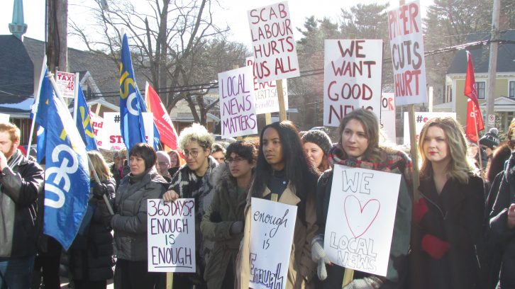 People of all ages gathered at the Chronicle Herald protest holding signs and flags.