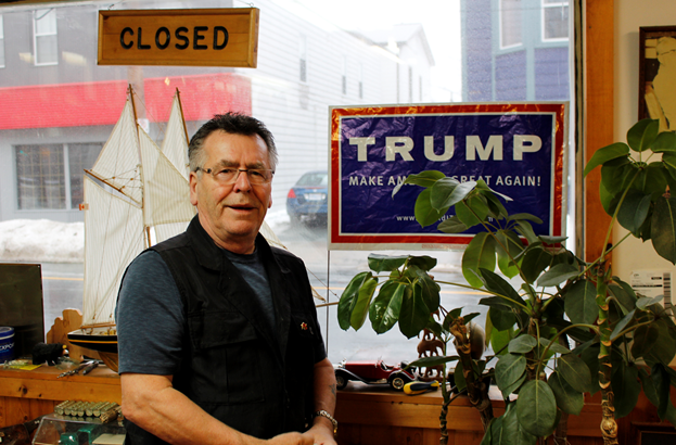 Leroy Bennett, owner of Bennett's Barbershop, standing next to his sign.