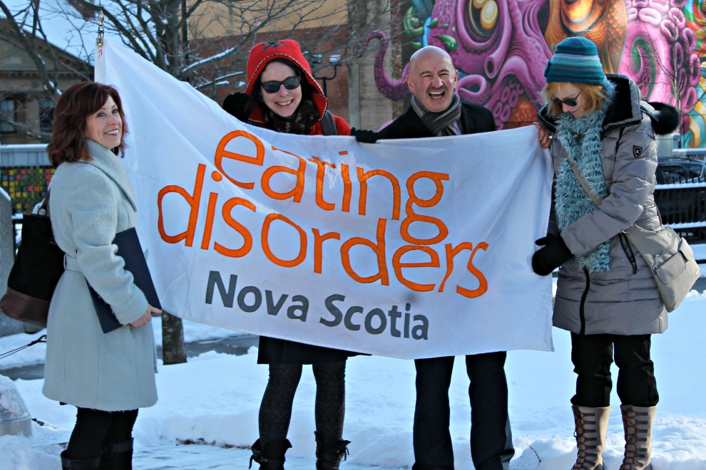 Members of Eating Disorders Nova Scotia get ready to raise the flag.