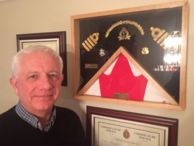 Ken Hoffer, founder of the Society of Atlantic Heroes, poses before Navy memorabilia at his home in Dartmouth