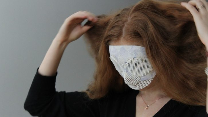 Milne tries on the lone mask-like headpiece for size.