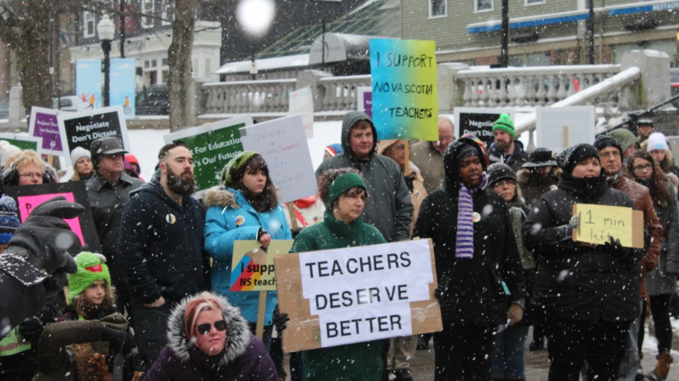 The engaged protesters hold up signs in favour of NS teachers.
