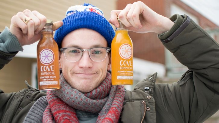 Cove Kombucha founder Ryan MacLellan holds up two of his drinks.