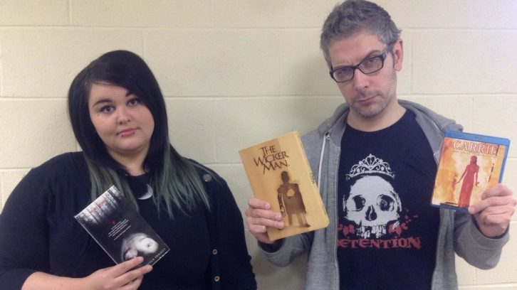 Thrillema volunteers Jess Smallwood and Mark Palermo hold up copies of their favorite horror movies.