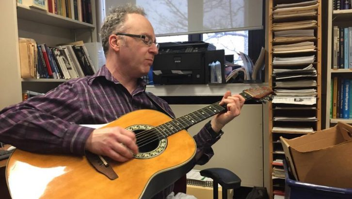 Professor Jason Brown playing guitar in his office.