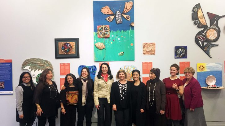Ten women artists are in front of their mosaic arts.