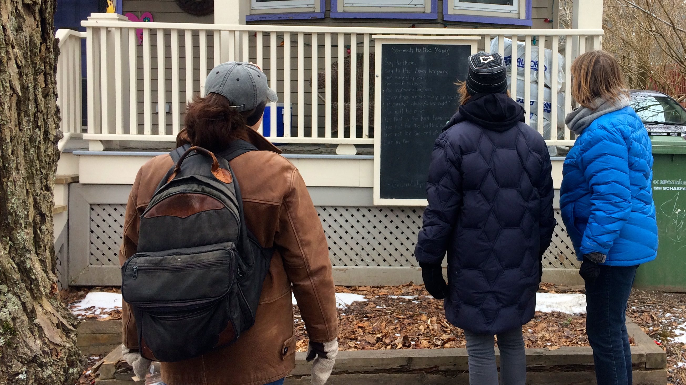 Lisa Johnson (left, with backpack) reads a poem on Harvard Street.