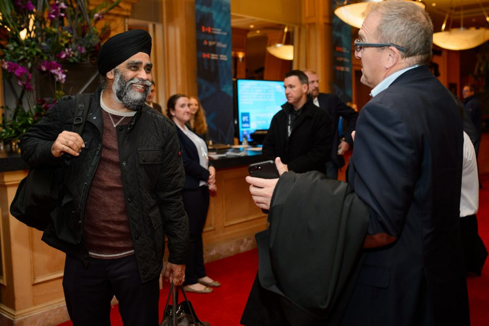Defence Minister Harjit Sajjan greets another participant in the hotel lobby