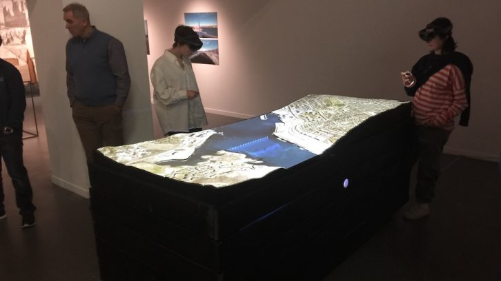 Two gallery visitors use augmented reality headsets to explore the site of the Halifax Explosion.