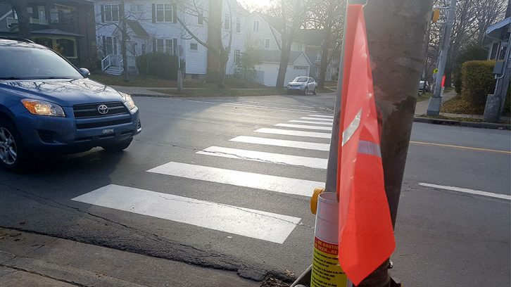 City staff recommended crosswalk flags be removed from locations with overhead amber lights.