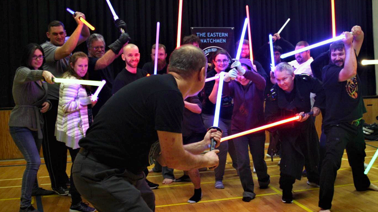 Founder of the Eastern Watchmen, Erik Bauckman, defends himself against the other members of the lightsaber dueling group.
