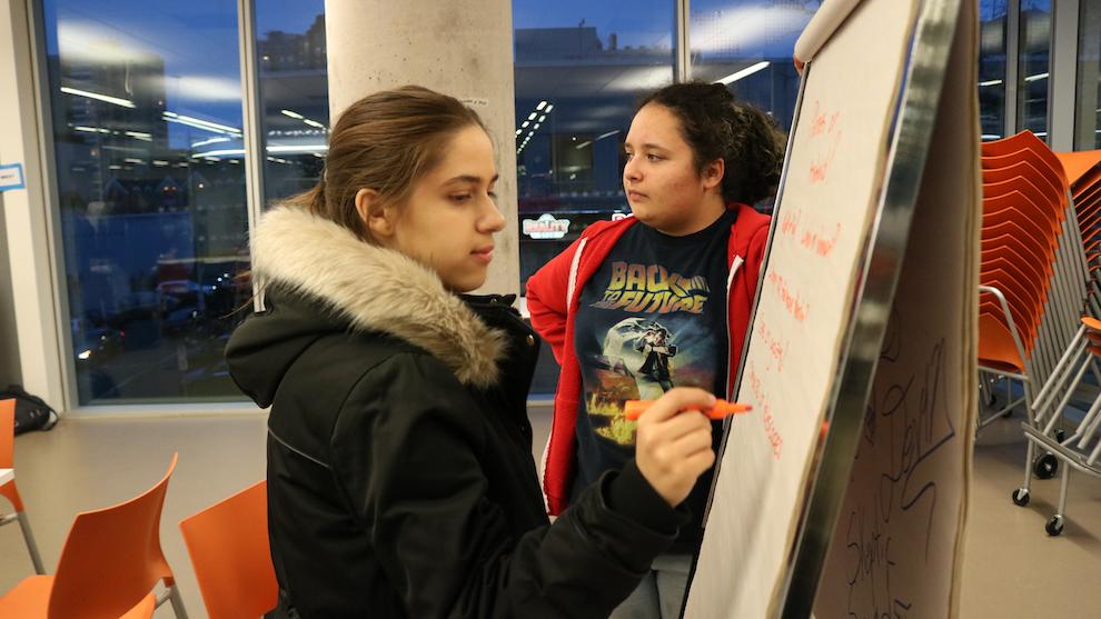 Rand Abounahia and Lola Cardona write down some ideas during the program meeting.