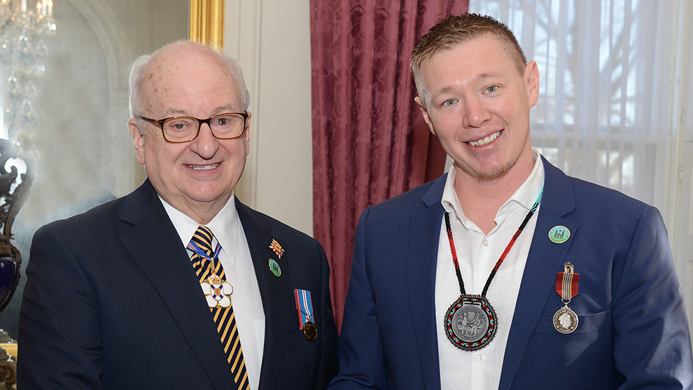 Jaime Battiste (right) receives the Sovereign's Medal for Volunteers from Lt.-Gov. Arthur J. LeBlanc (left).