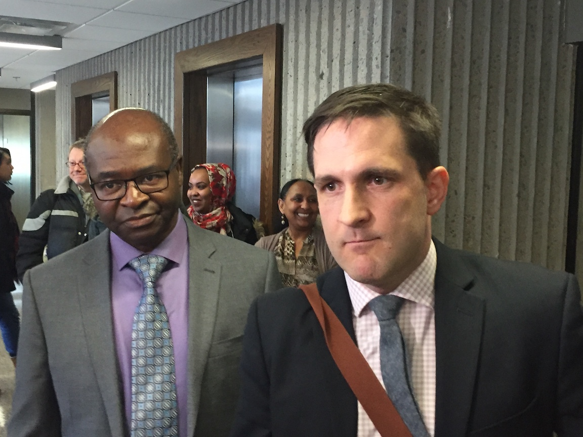 Abdoul Abdi's attorney Benjamin Perryman (right) speaks to reporters outside of the courtroom.