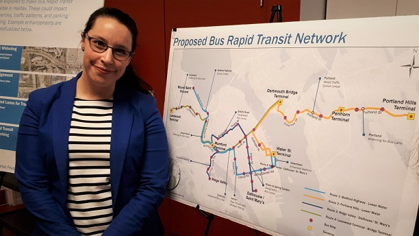 Erin Sway stands next to a map showing the four proposed BRT routes.