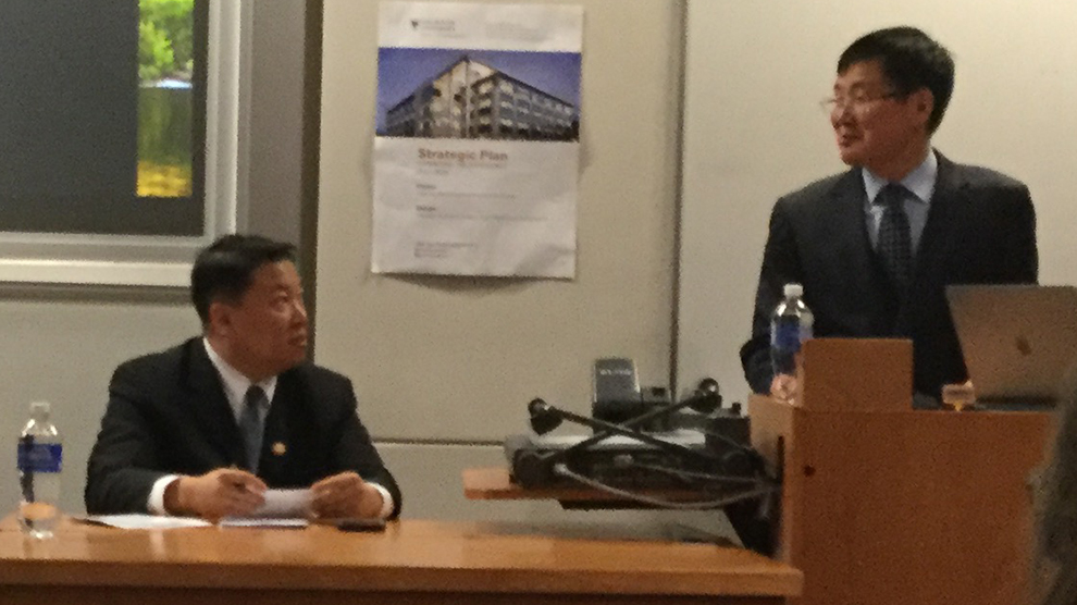 Henry Song, left, translates Jung Gwang-Il's words from Korean to English.