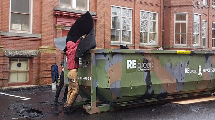 A worker tosses roofing felt from the conservatory into a bin