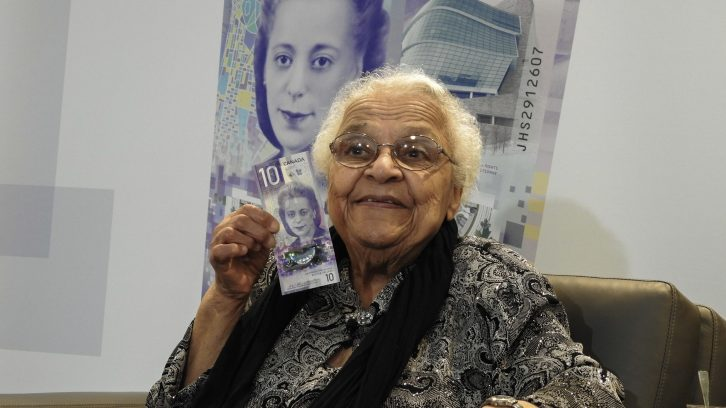 Wanda Robson poses with the $10 bill featuring a portrait of her sister.