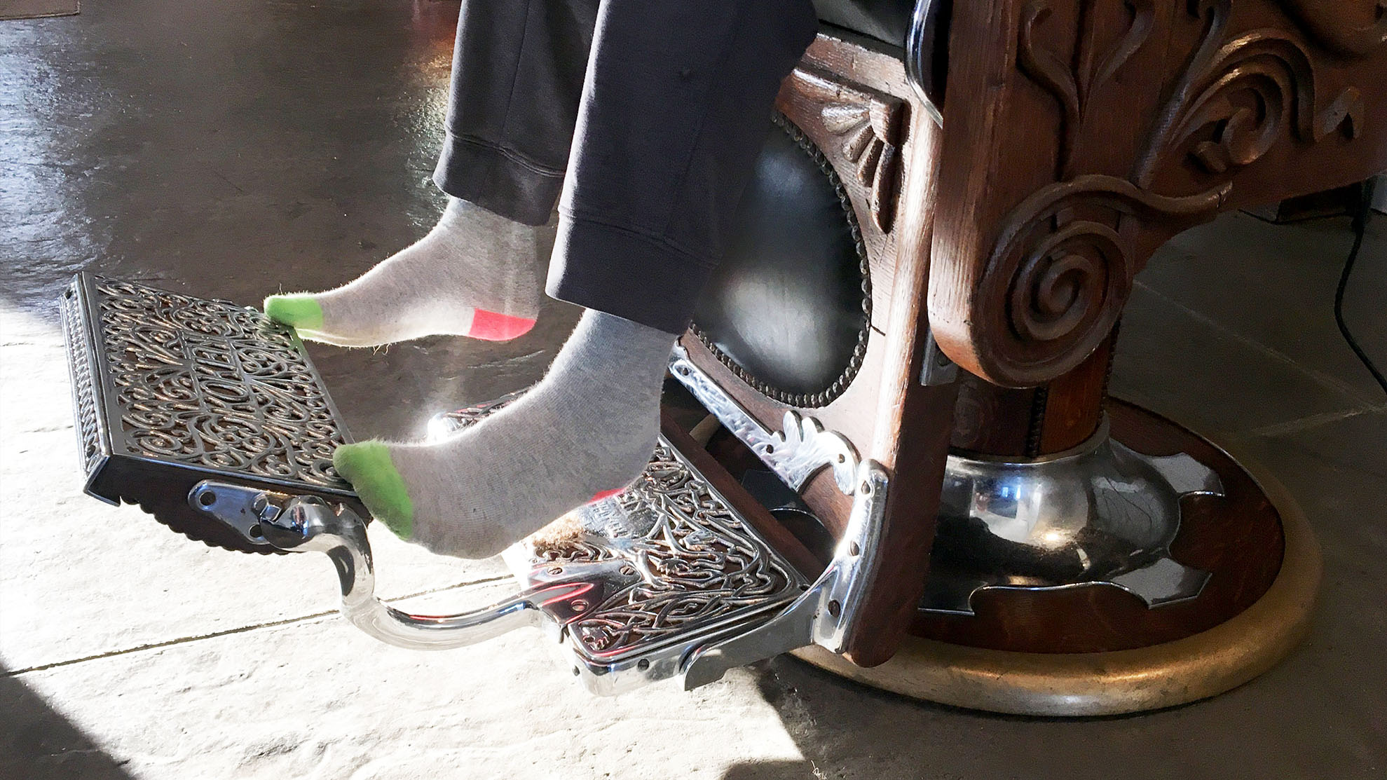 Eleven-year-old Josiah Brown's feet just reach the chrome foot pedal of Jack Desmond's barber chair.