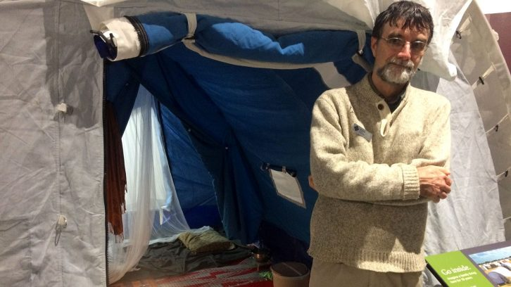 Museum curator Dan Conlin stands alongside a UNHCR tent featured in Refuge Canada exhibit