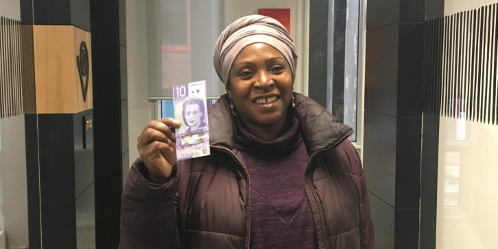 """Afua Cooper holds up her new Viola Desmond bill at the Delmore """"Buddy"""" Daye Learning Institute."""