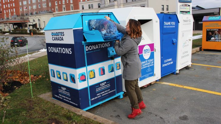 Sadie Hirschfield donates a bag full of clothing at one of Diabetes Canada's drop-off boxes.