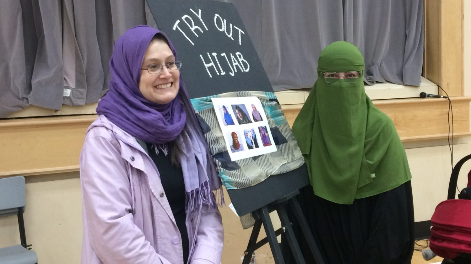 Alex Holmberg (left) tries on the hijab at Arazoo Hoseyni (right)'s table