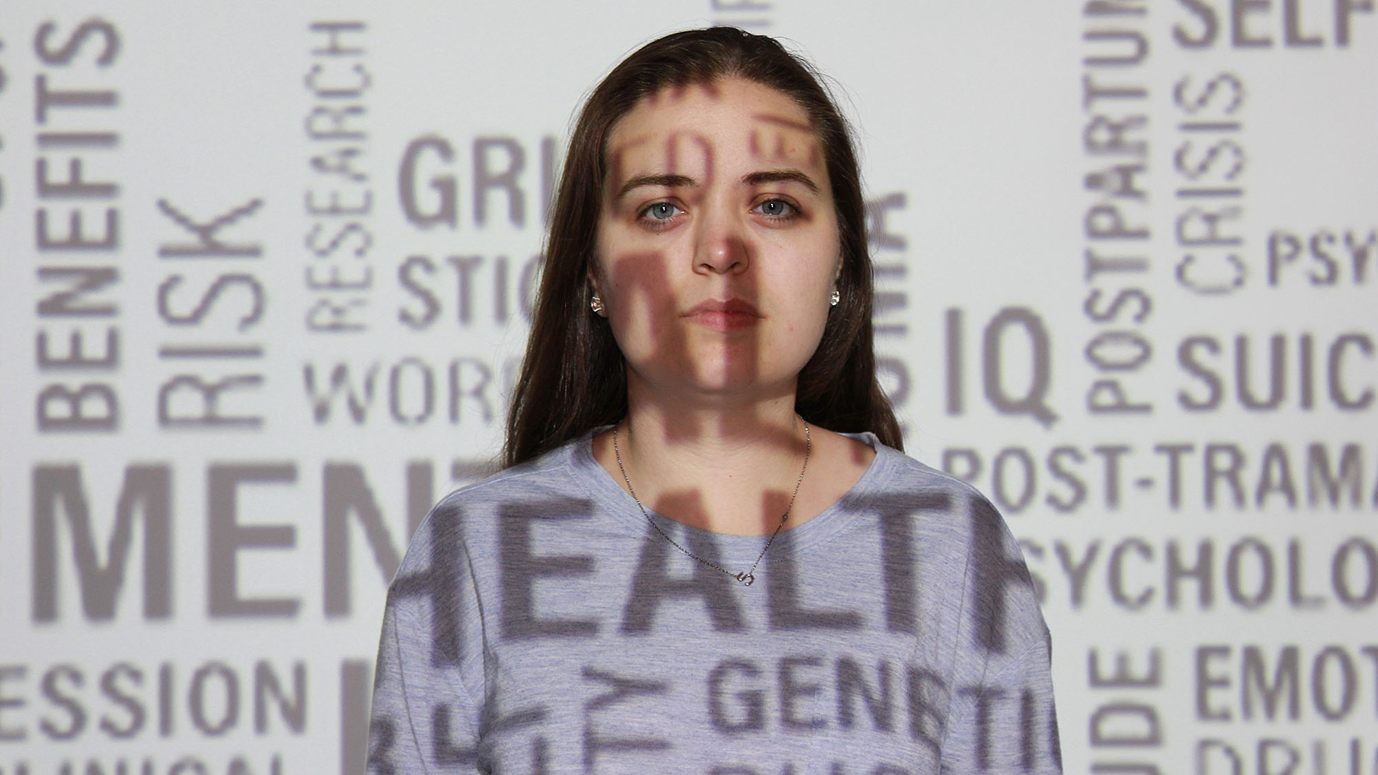 A model is projected with words related to mental health.