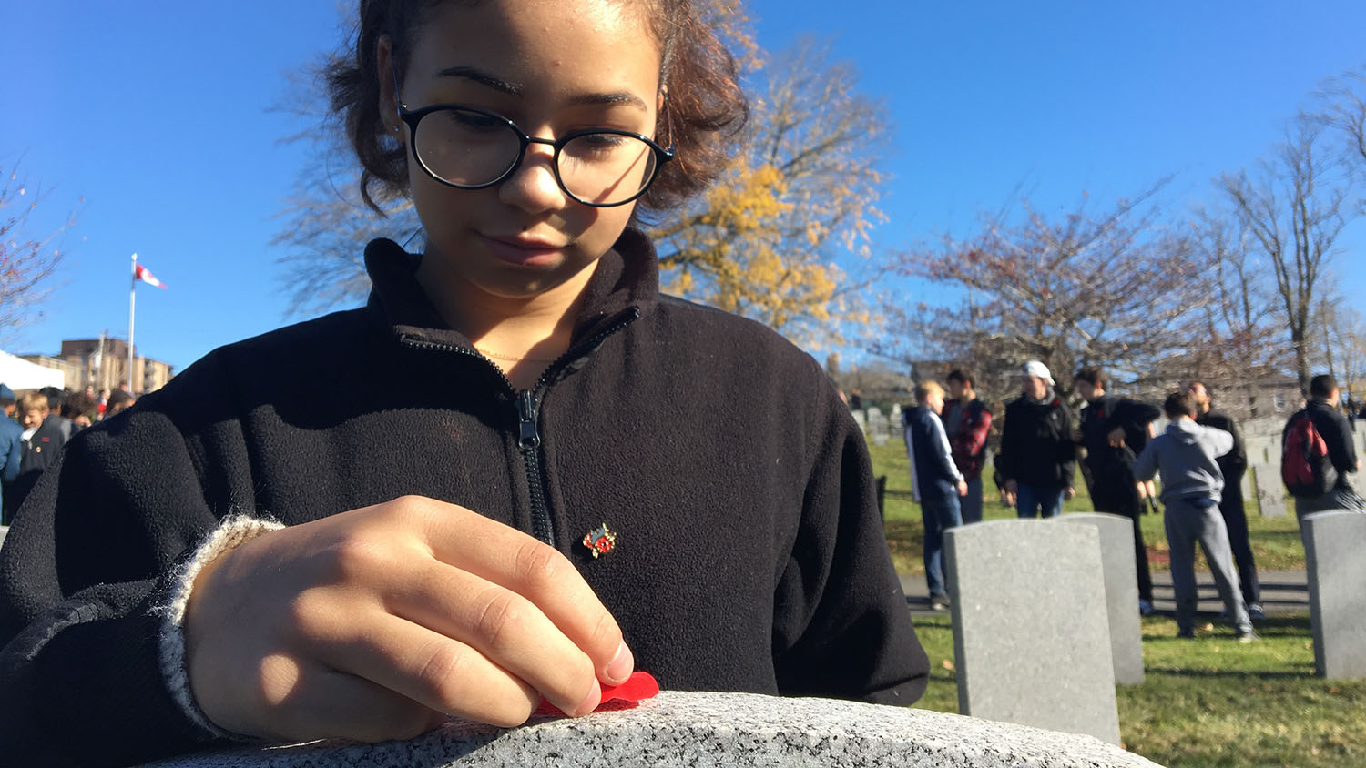 Carina Rolfe, 14, lays a poppy on Pte. Wallace Lamrock's grave at Fort Massey Cemetery.