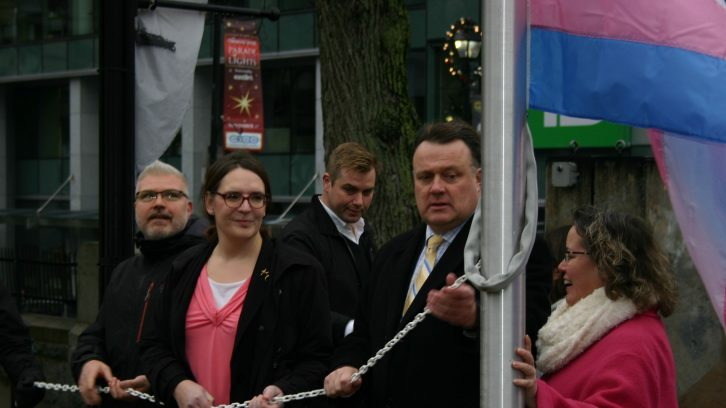 Shawn Cleary, Jessica Dempsey, and Mayor Mike Savage raise the transgender flag outside of Halifax City Hall on Tuesday. Nov. 20 is Trans Day of Remembrance.