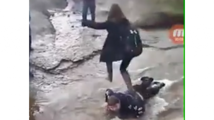 A screen grab from the original video showing a female student walking over Corbett's back