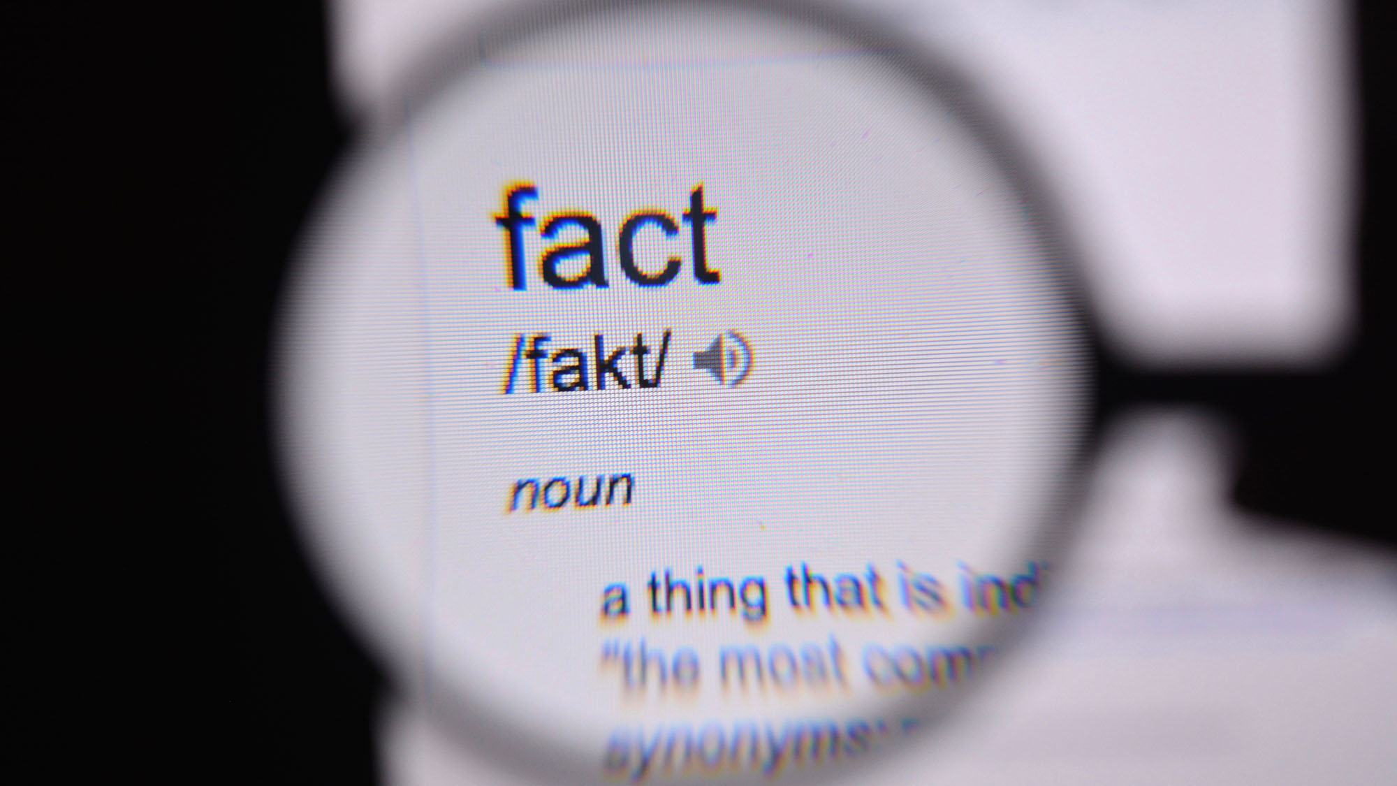 A person looks through a magnifying glass at the definition of the word fact.