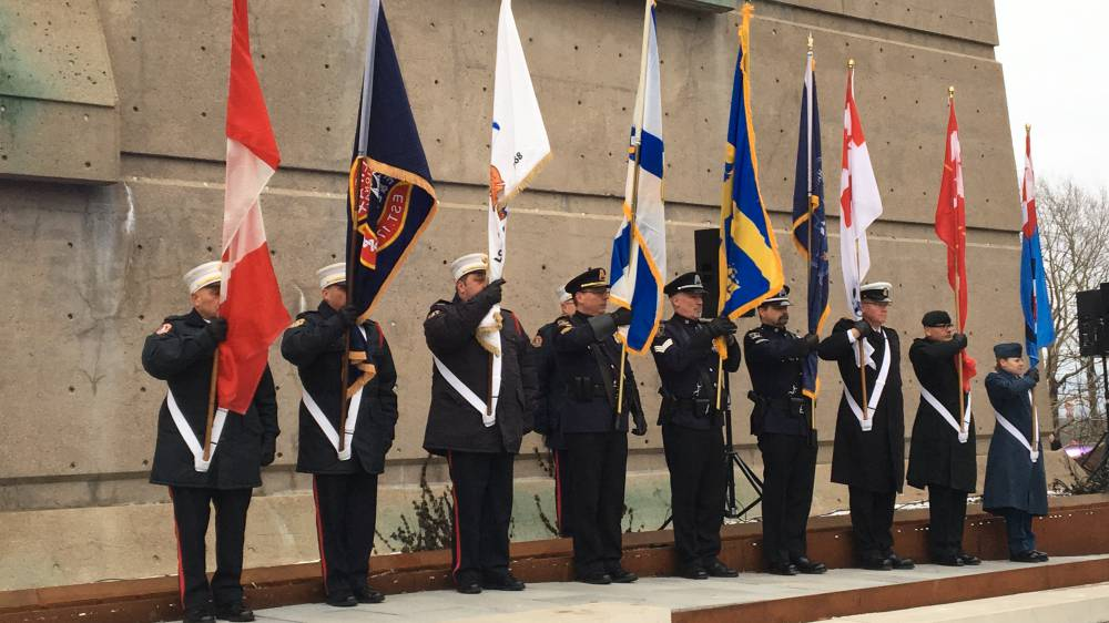Military members hold flags in front of the Fort Needham Bell Tower during a ceremony marking the 101st anniversary of the Halifax Explosion.