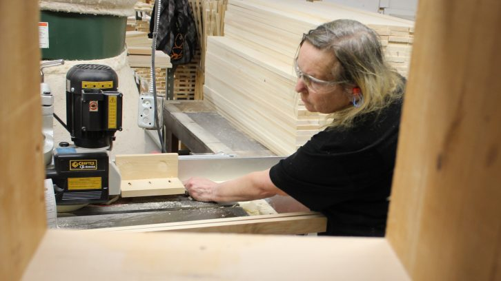 Kim Shaw uses a table saw to trim a wooden wine rack leg at LakeCity Woodworkers.