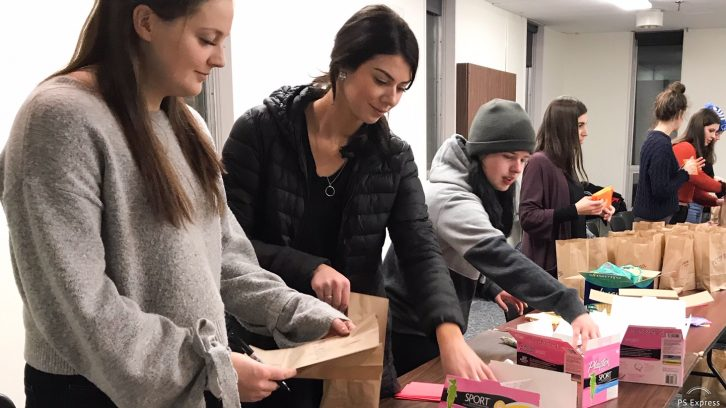 Volunteers pack menstrual products in bags for Halifax shelters.
