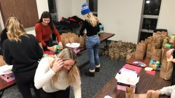People are packing brown paper bags with menstrual products.