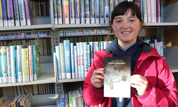 Alice Roebotham, 10, holds her book I Survived the Halifax Explosion.