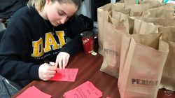 Person writing notes with paper bags on a table.