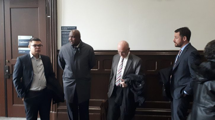 Const. George Edward Farmer, second from the left, stands with his legal team, right and a supporter, left, before entering the courtroom Jan. 18, 2019