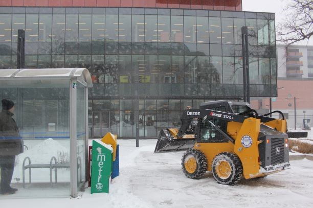 Plow clears snow in front of Halifax Central Library while someone observes.