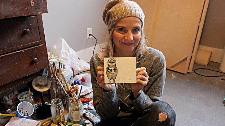 Woman holds painting next to paint brushes